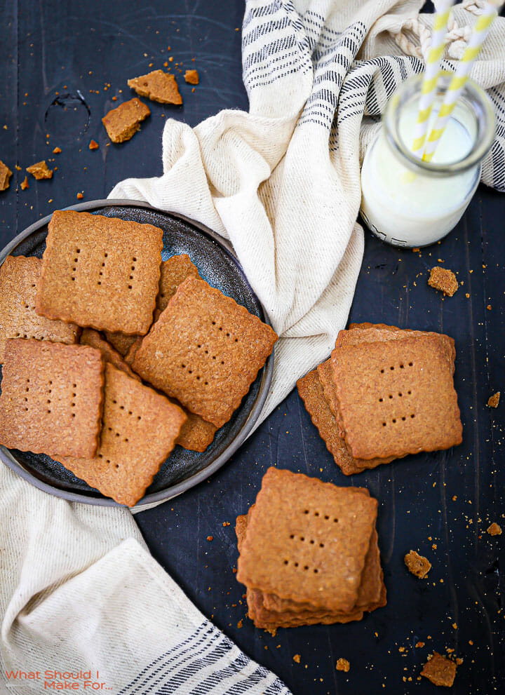 Two stacks of Homemade Graham Crackers on a black table top with crumbs scattered around and a plate of crackers and milk next to them..