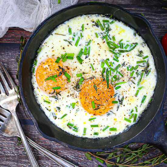 Skillet Baked Eggs sprinkled with chives and herbs, with two forks and fresh thyme scattered around.