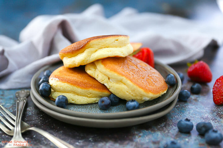 Fluffy Japanese Pancakes on plate with blueberries and strawberries around.