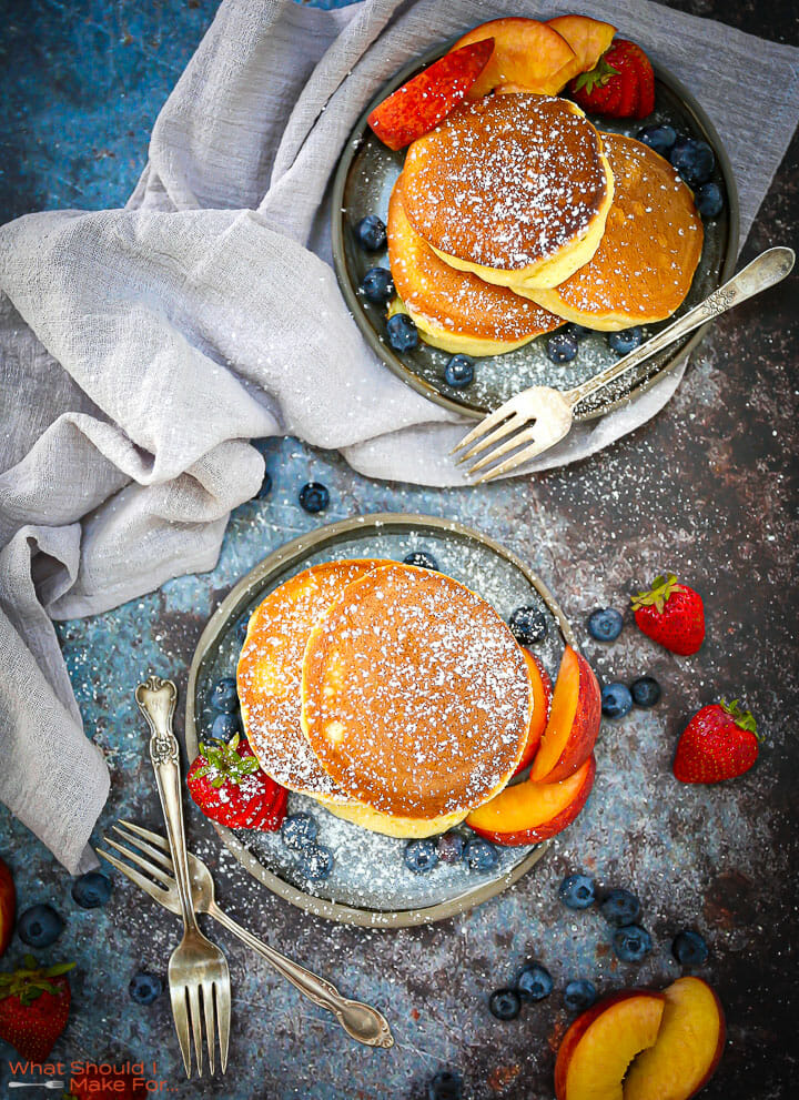 Fluffy Japanese Pancakes on two blue plates dusted with powdered sugar with peaches and berries scattered around.