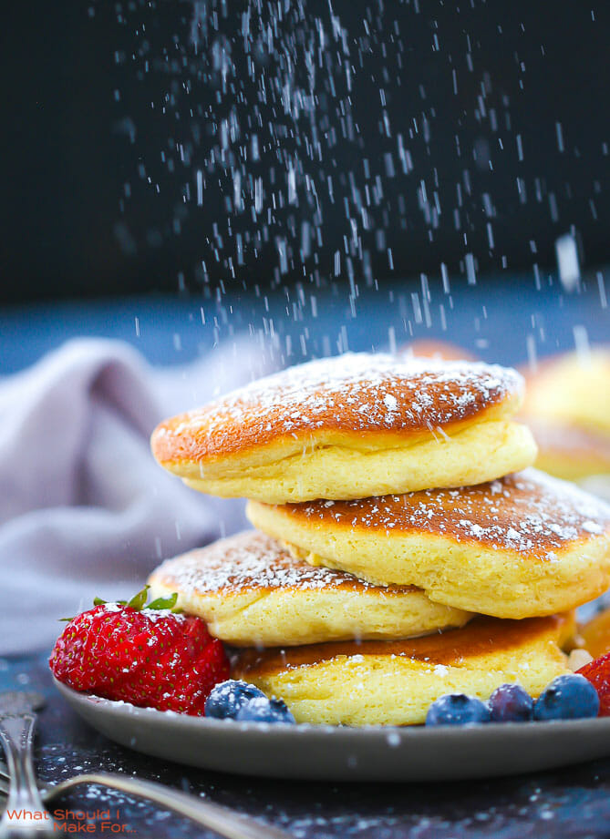 A stack of Fluffy Japanese Pancakes being dusted with powdered sugar.