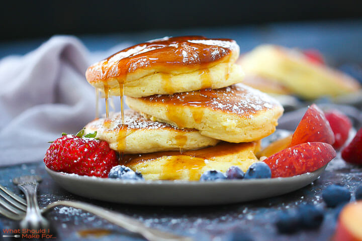 A stack of Fluffy Japanese Pancakes topped with powdered sugar and syrup with berries on the plate.