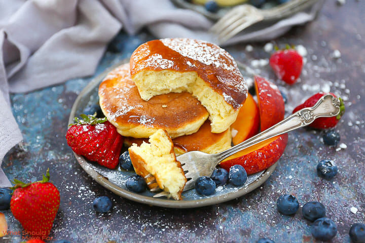 Fluffy Japanese Pancakes on a plate with a bite on a fork with berries and powdered sugar.