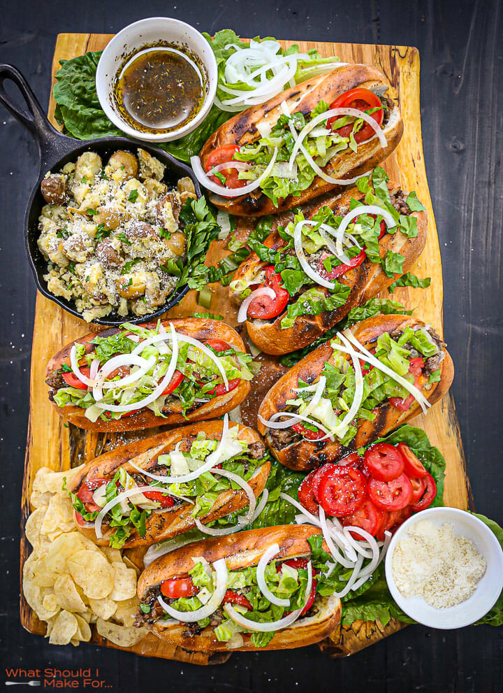 Six Cheeseburger Subs on a wooden board with a chops, sub sauce and a skillet of potatoes on it.