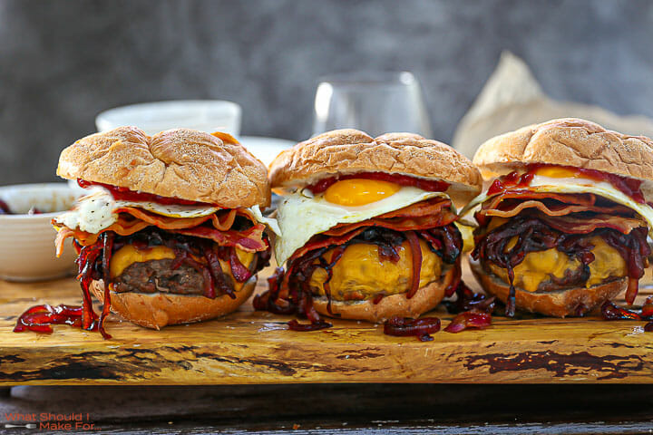 Three Egg Topped Bacon Cheeseburgers on a would board with ketchup in the background.