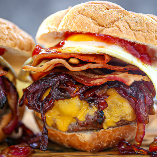 Close up of a Egg Topped Bacon Cheeseburger piled high with sautéed onions.