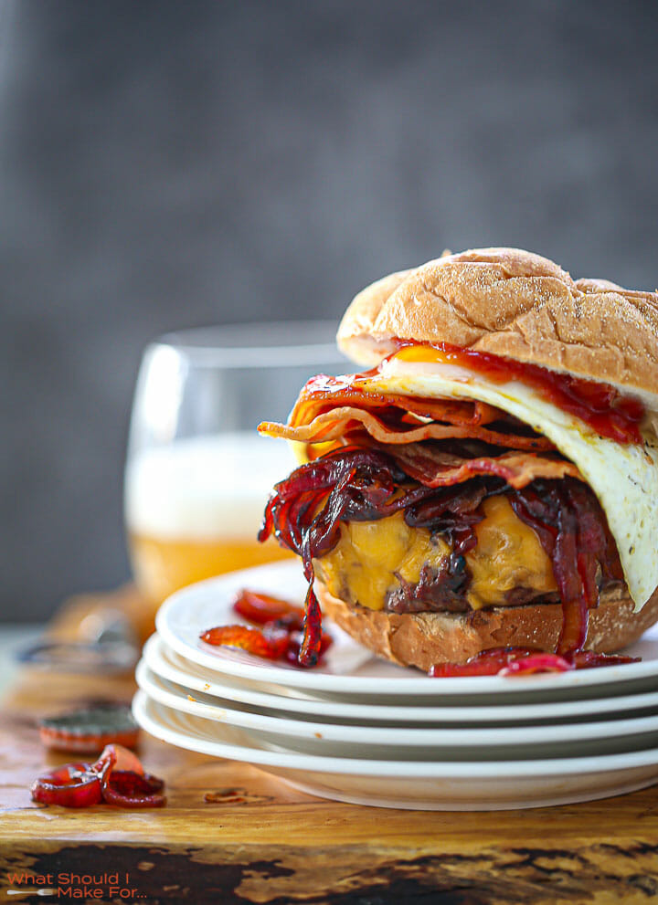 Egg Topped Bacon Cheeseburger on a stack of white plates with a glass of beer in the background.