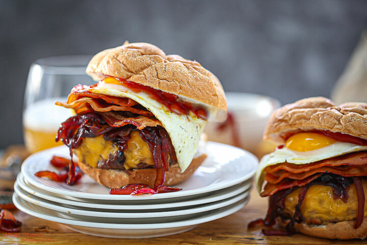 Two Egg Topped Bacon Cheeseburgers on a stack of white plates with a beer in the background.