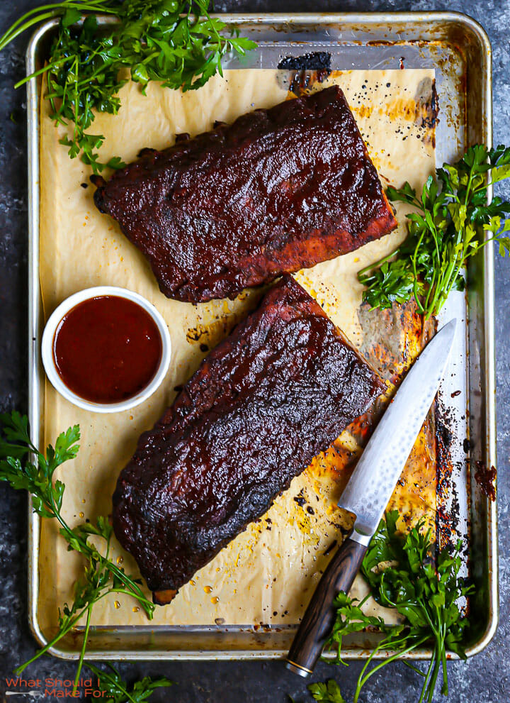 Baby Back Ribs with Bourbon BBQ Sauce on a sheet tray with herbs scattered around.