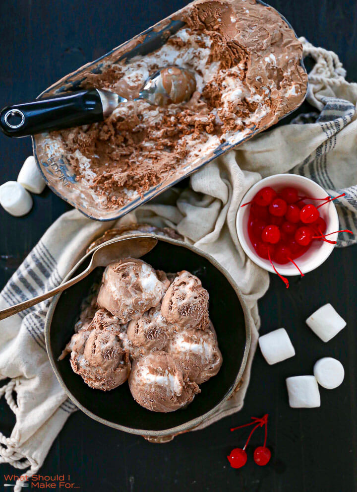 Overheard shot of Chocolate Marshmallow Swirl Ice Cream in a bowl and serving dish with cherries and marshmallows scattered around.