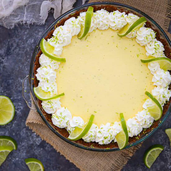 Overhead shot of a key lime pie decorated with whipped cream and fresh limes.