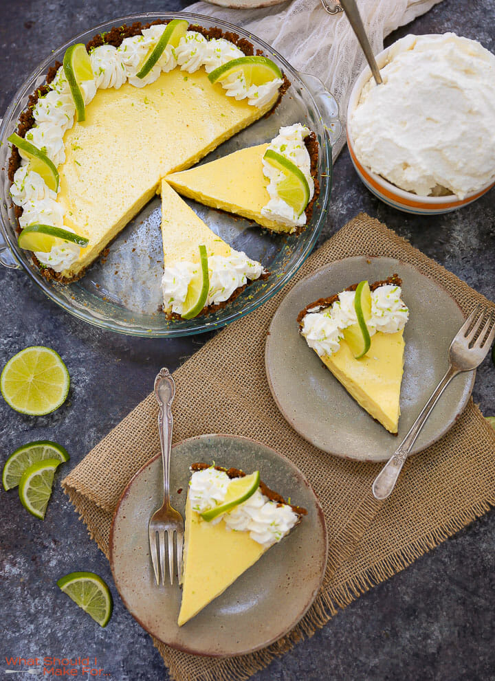 Two slices of Key Lime Pie on plates with the cut pie and bowl of whipped cream on the table.