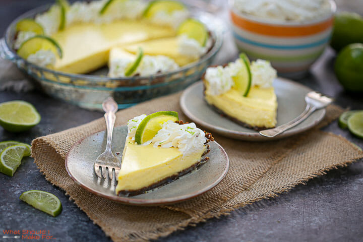 A slice of Key Lime Pie on a plate with the cut pie in the background.