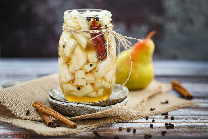 Quick Pickled Pears in a mason jar with cinnamon sticks and a pear in the background,