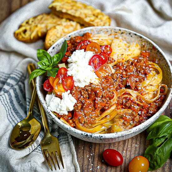 A bowl of fettuccine with bolognese sauce, fresh ricotta, and tomatoes with parmesan crisps in the background.