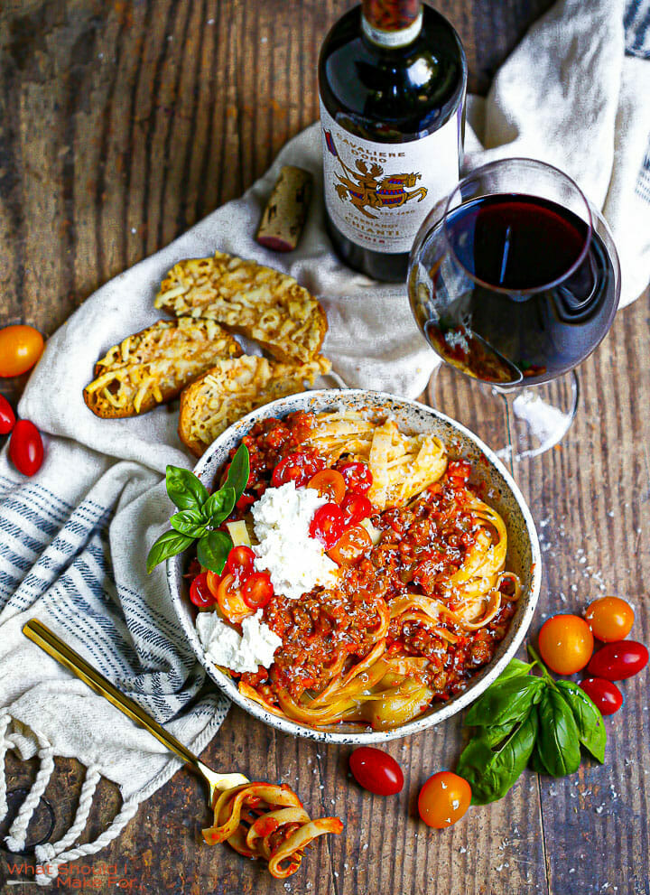 A bowl of fettuccine with bolognese sauce, fresh ricotta, and tomatoes served with parmesan crisps and Chianti.