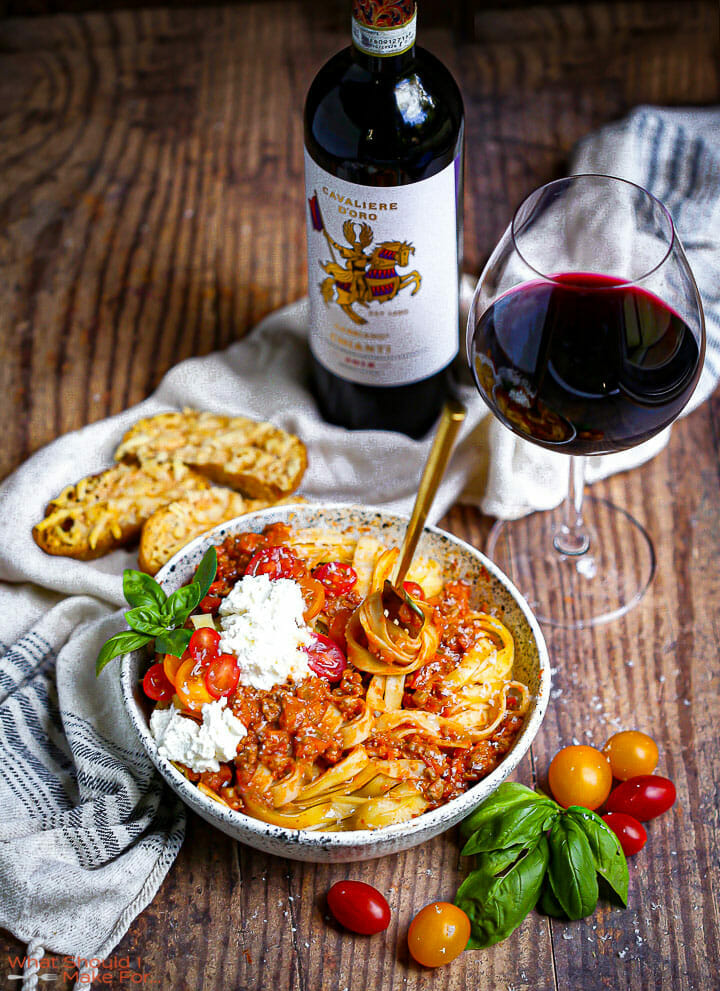 A fork stuck in a bowl of fettuccine with bolognese sauce, fresh ricotta, and tomatoes served with Chianti.