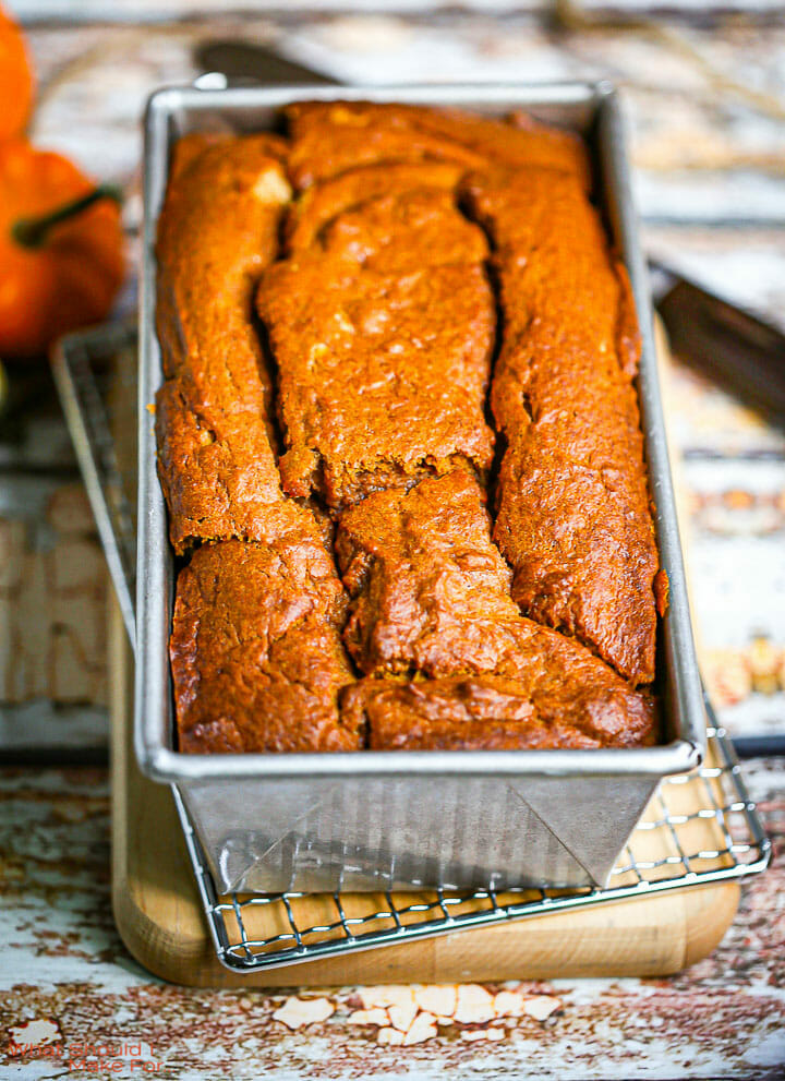 A loaf of pumpkin bread in the baking pan on a rack and cutting board.