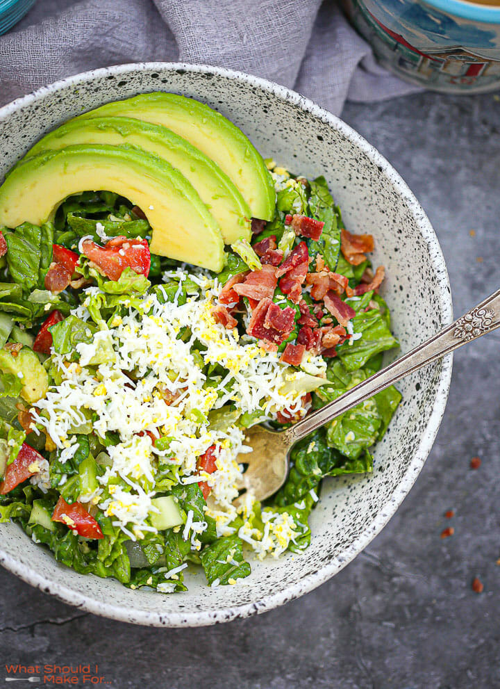 A serving of Chopped BLT Breakfast Salad in a speckled bowl with a fork.