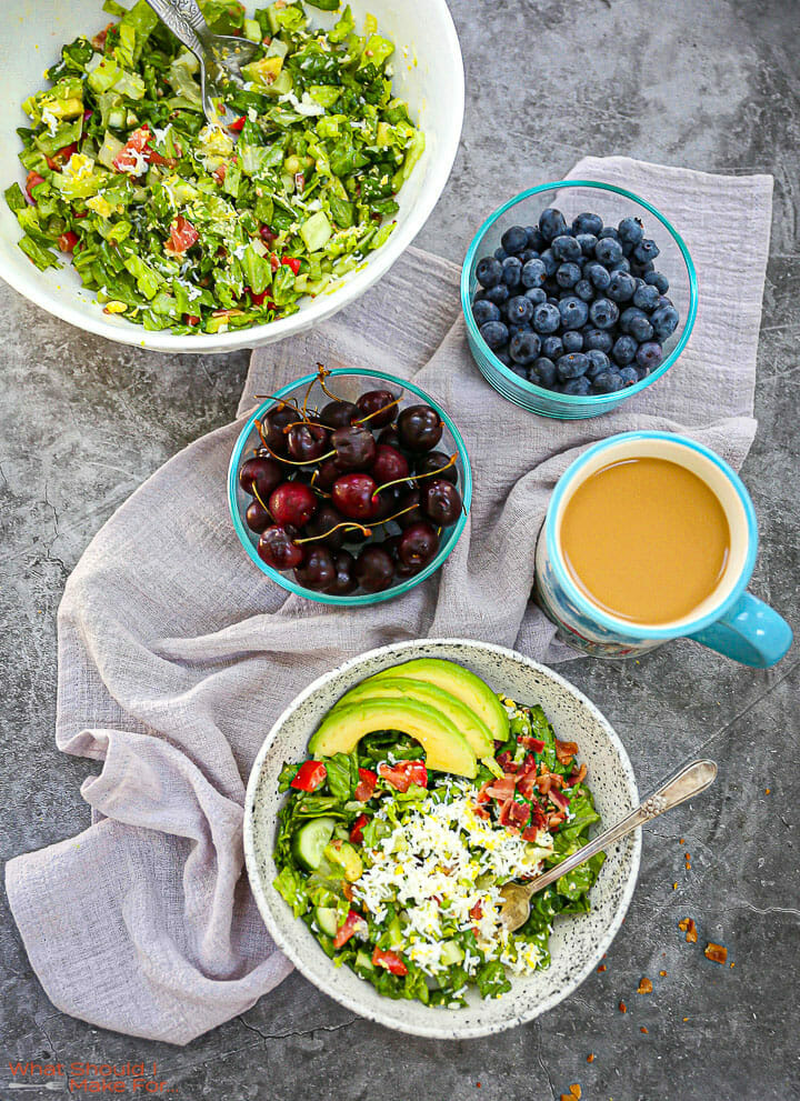 A serving of Chopped BLT Breakfast Salad on the table with coffee, cherries, blueberries and a the serving bowl of salad.