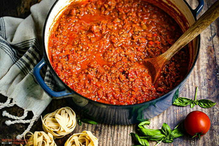 Bolognese Sauce in a dutch oven with fresh basil and nests of uncooked fettuccine on the table