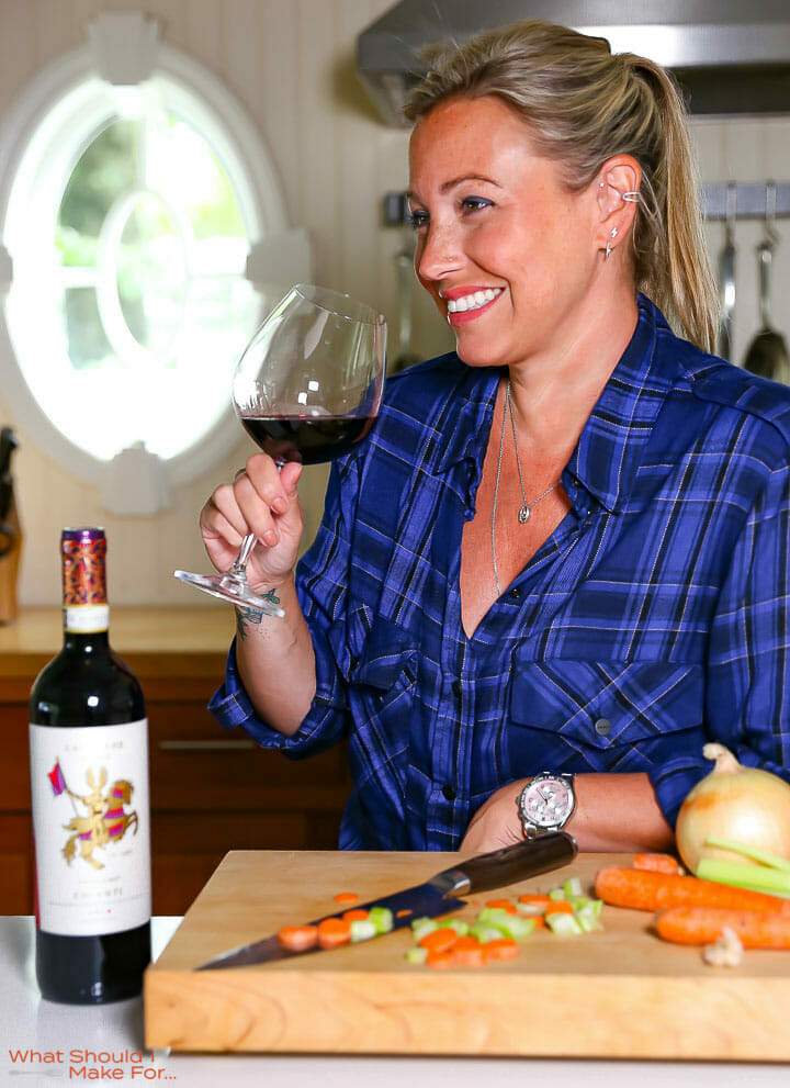 Cathy Roma enjoying a glass of Chianti while cooking homemade Bolognese sauce.