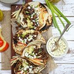 Slow Roasted Lamb Tacos on a long wooden board with apples. scallions, and feta cheese on the table.