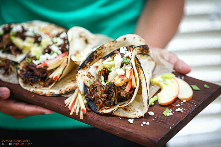 Someone holding Slow Roasted Lamb Tacos on a wood board.