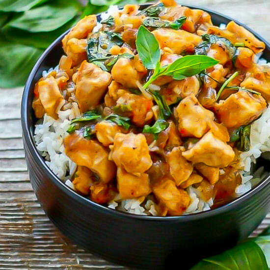 Thai Basil Chicken in a black bowl served over rice and garnished with basil.