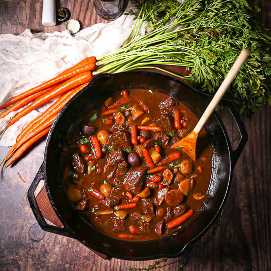 Guinness Braised Beef Stew in a cast iron dutch oven with a wooden spoon in the pot.
