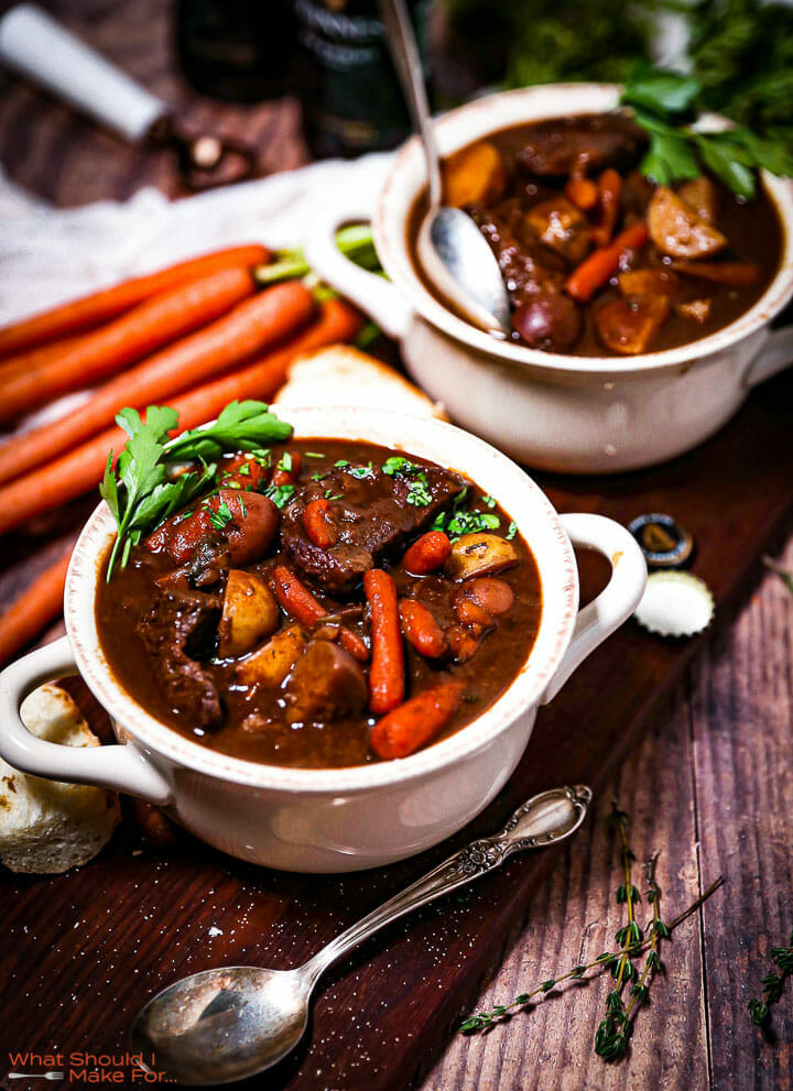 Two servings of Guinness Braised Beef Stew in crocks next to carrots and spoons.