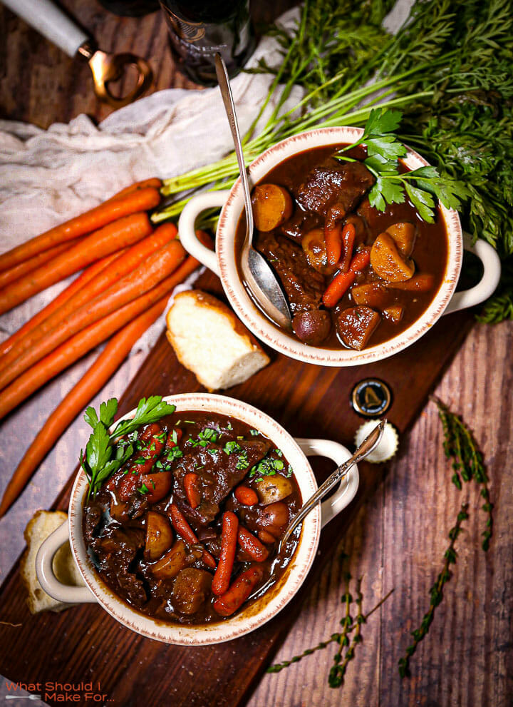 Two servings of Guinness Braised Beef Stew in crocks next to carrots with green tops.