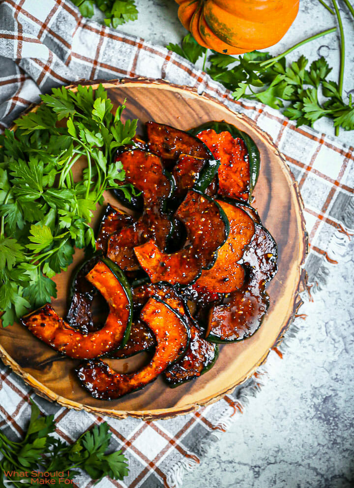 Sweet and Spicy Acorn Squash on a round wood board on a plaid towel with a scattering of parsley