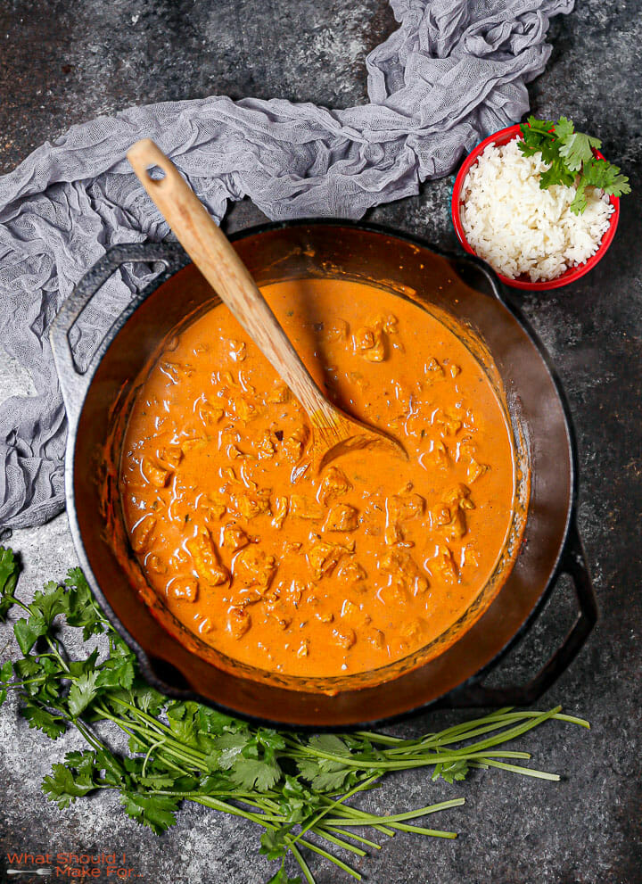 Easy Butter Chicken in a cast iron pot with rice and cilantro alongside.