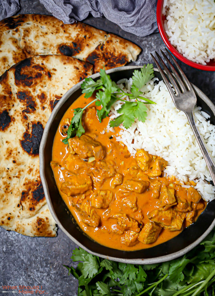 Overhead shot of a bowl of Easy Butter Chicken with a cilantro garnish and charred naan.