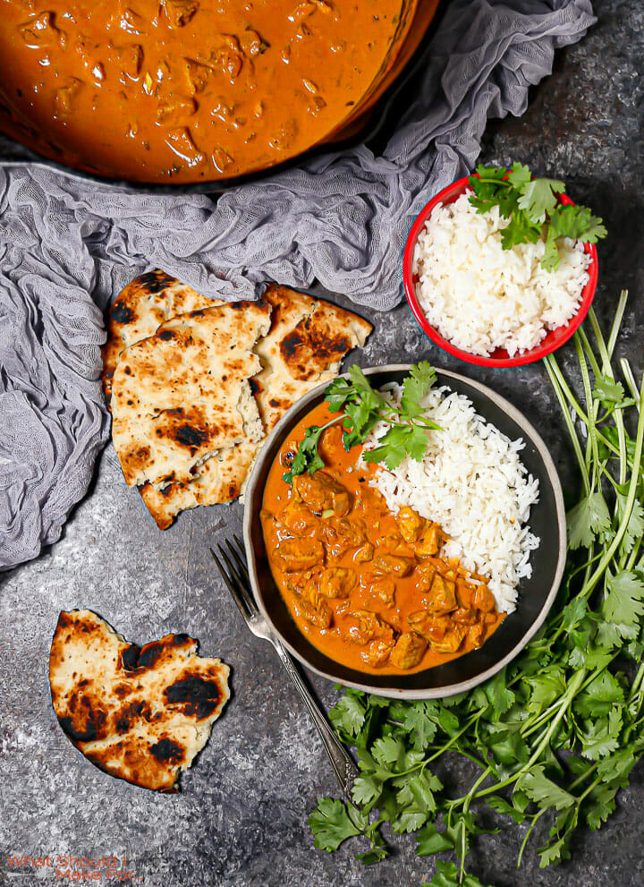 A serving of Easy Butter Chicken in a black bowl with naan and cilantro scattered around.