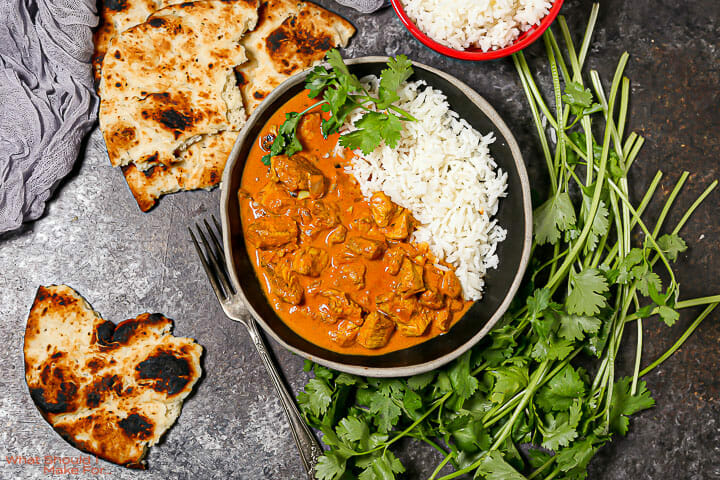 A bowl of Easy Butter Chicken served with rice, naan and cilantro.