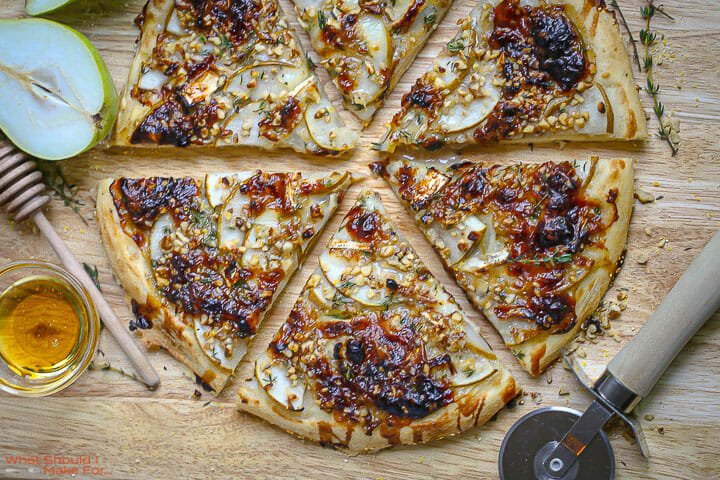 Pear and Brie Pizza sliced on a cutting board with honey and a pizza cutter on the board.