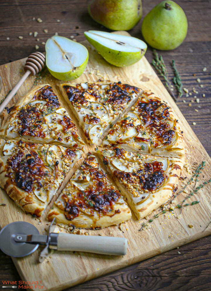 Pear and Brie Pizza sliced on a cutting board with pears and walnuts scattered around.