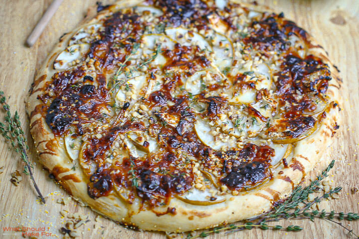 Close up of a Pear and Brie Pizza with thyme scattered around.