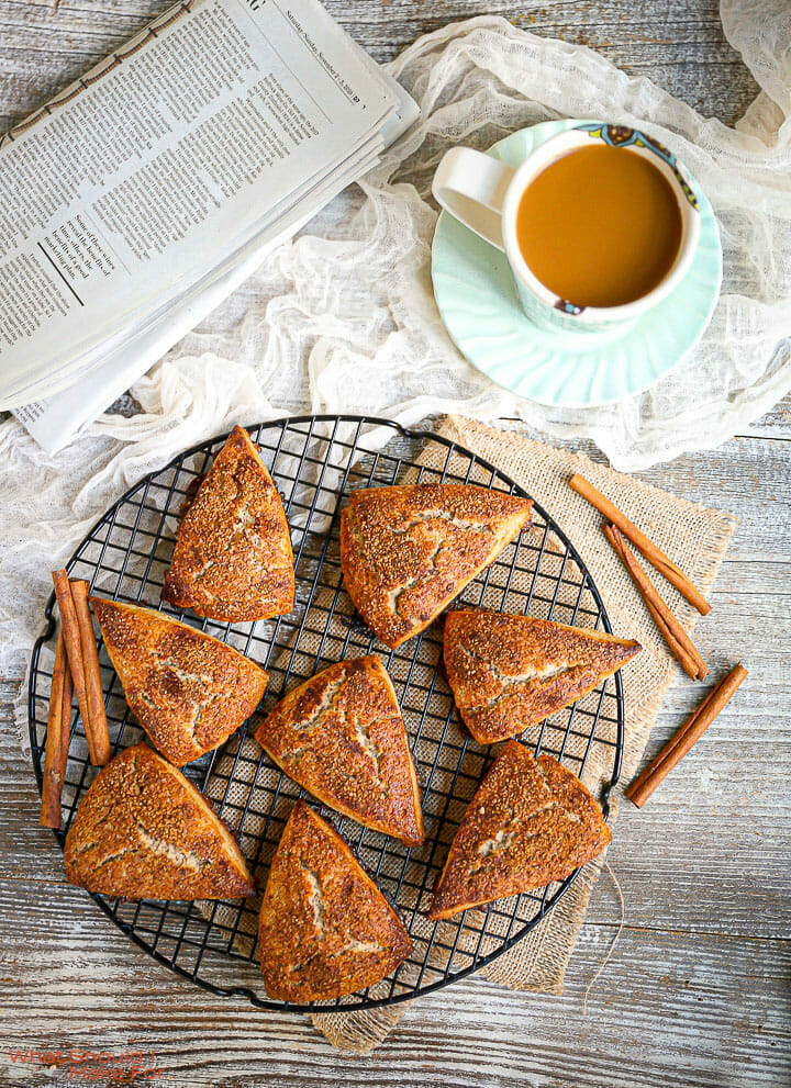 Cinnamon Sugar Scones on a round wire rack with a cup of coffee and a newspaper on the table.