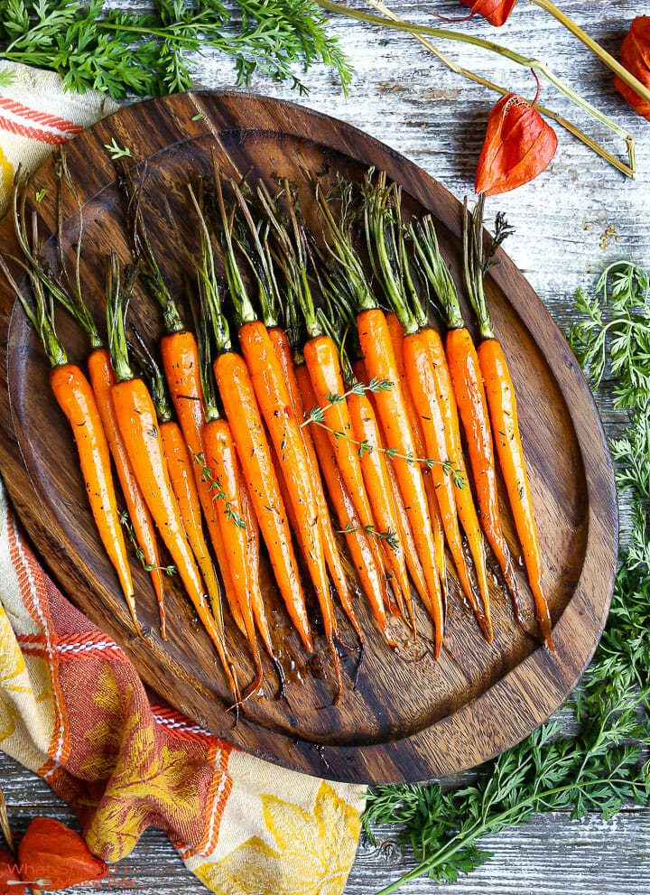 Honey Glazed Carrots on an oval serving tray on top of a festive linen with greens scattered around.