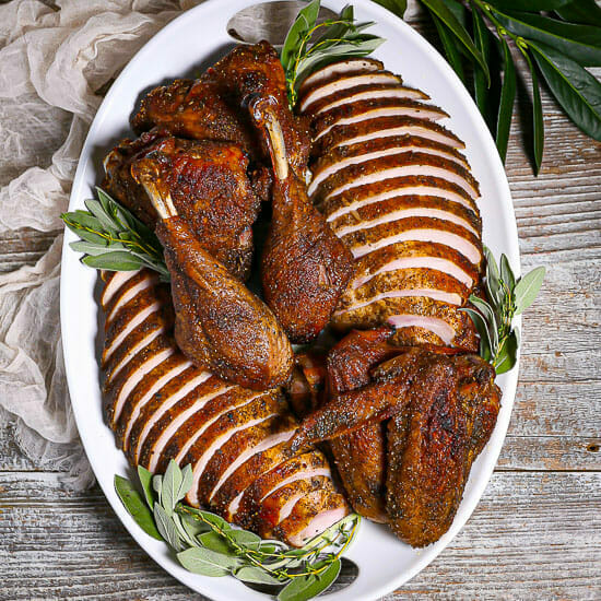 Roast Turkey in Parts on a white oval serving platter with sage.