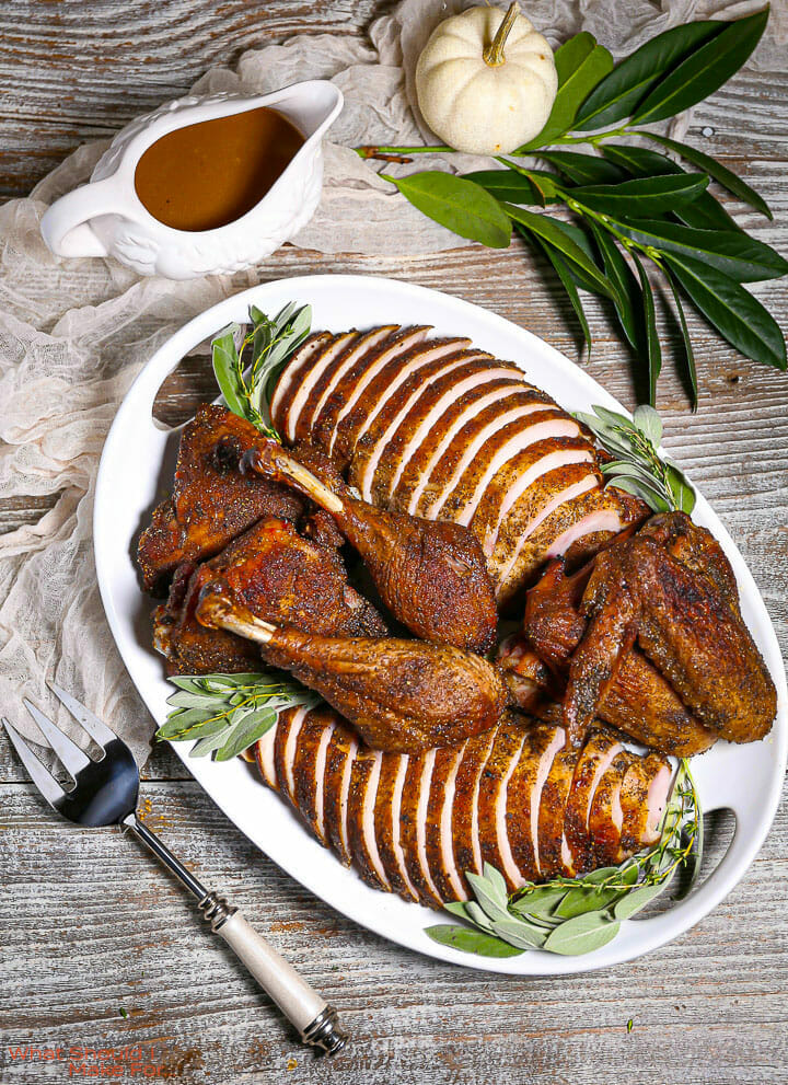 Roast Turkey in Parts on a serving platter with a gravy boat, greenery, and a serving fork on the table.