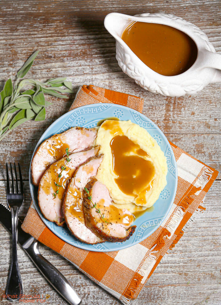 Make-ahead turkey gravy in a gravy boat and served over turkey and mashed potatoes.