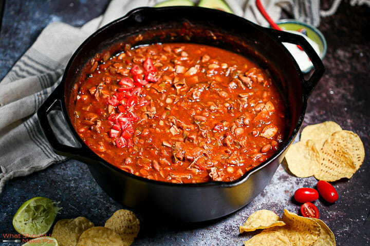 A pot of leftover turkey chili in a cast iron dutch oven.