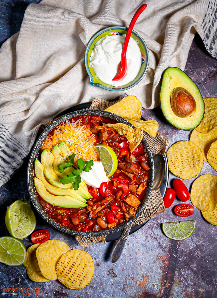 A bowl of leftover turkey chili garnished with chips, a bowl of sour cream and garnishes strewn around.