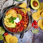 One serving of leftover turkey chili in a bowl with chips and garnishes scattered around.