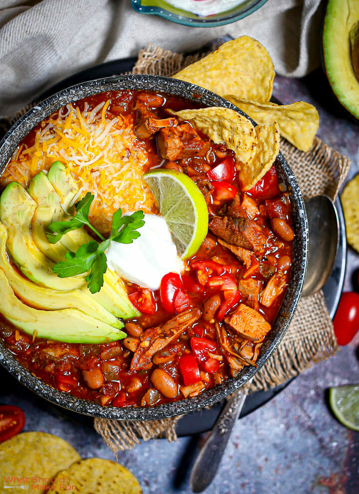 A bowl of Leftover Turkey Chili garnished with avocado, cheese, sour cream and limes.