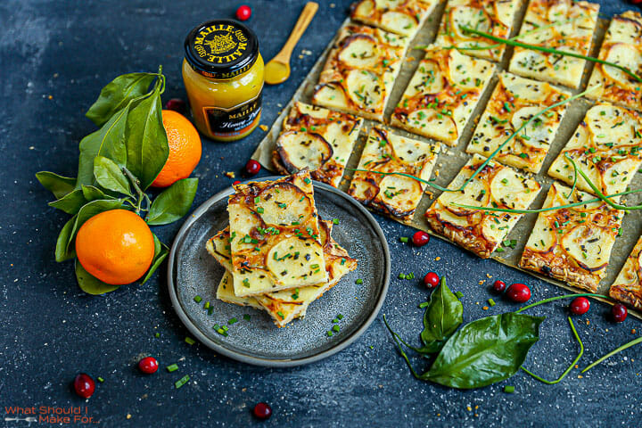 Honey Mustard Potato Tart on a black board cut into squares with one serving on a small plate.